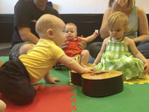 Babies in music class crawl to guitar. Royalty Free Stock Photos