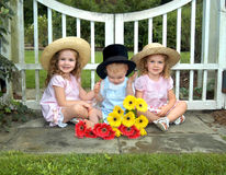 Babies at my gate. Three small children sit in front of white wooden gate.  Alll are wearing hats.  Boy struggles with his top hat Royalty Free Stock Photo