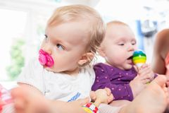 Babies with pacifier in toddler group playing with toys. Babies with pacifier in toddler group playing together with toys Royalty Free Stock Photos