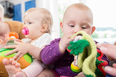 Babies with pacifier in toddler group playing with toys Royalty Free Stock Photography