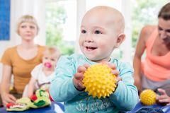 Babies with pacifier in toddler group playing with toys. In baby course Stock Images