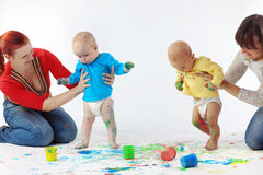 Babies painting with parents. Two babies painting with parents Stock Photos