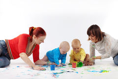 Babies painting with parents. Two babies painting with parents Stock Photography