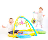 Babies play with toys. One year old babies (a boy and a girl) enjoy playing with toys. Studio Shot. All toys visible on the photo are officialy property released stock photos