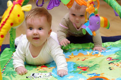 Babies playing. Two babies playing in educational mat Royalty Free Stock Image