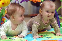 Babies playing. Two babies playing in educational mat Stock Image