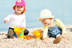 Babies playing on the beach Royalty Free Stock Photos