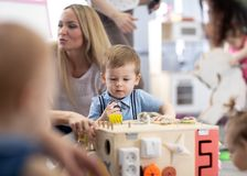 Babies playing in daycare centre or nursery stock image