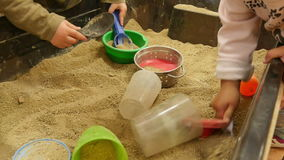 Babies Playing with Sand in Kindergarten Childcare. Children digging with many colorful toys on the sandbox. Fun school activities for babies and kids stock video footage