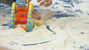 Babies Playing with White Flour in Kindergarten Childcare. Children playing with flour and many colorful toys on the flourbox. Fun school activities for babies stock video footage