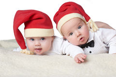Babies with santa hats on bright background royalty free stock images