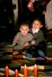 Babies sitting on  floor near fireplace. On Christmas Eve Stock Photos