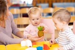 Babies som lär att spela för frukter, leker med läraren i barnkammare arkivfoto
