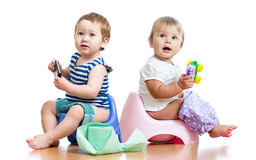 Babies toddlers on chamber pot and playing. Babies toddlers sitting on chamber pot and playing with toys royalty free stock images