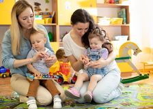 Babies toddlers playing with colorful educational toys together with mothers in nursery room. Babies toddlers playing with colorful educational toys together royalty free stock photography