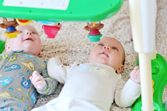 Babies with toy. Baby girl and baby boy are looking on the toy royalty free stock photos