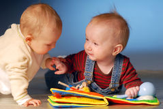 Babies with toys. Babies playing with toys on floor Royalty Free Stock Photos