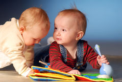 Babies with toys. Babies playing with toys on floor Stock Photos