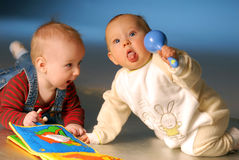 Babies with toys. Babies playing with toys on floor Stock Photo