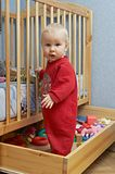 Babies and toys. Baby standing in the box with his toys Royalty Free Stock Image