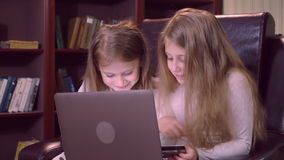 Babies use computer at home. Two caucasian sisters with long blond hair shopping online. Small girl sitting on the chair using laptop and holding credit card stock video