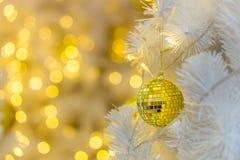 Babiole en verre de Noël sur la branche blanche d'isolement sur le fond jaune de bokeh d'éclat Photographie stock libre de droits