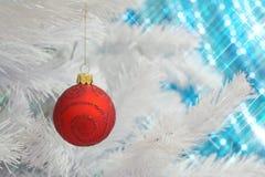 Babiole en verre rouge de Noël d'ornement de scintillement accrochant sur un arbre de Noël blanc Photographie stock libre de droits