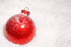 Babiole rouge de Noël sur un bâti de neige Photo libre de droits