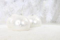 Babioles de Noël blanc dans la neige Photos stock