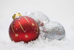 Babioles de Noël dans la neige Photographie stock