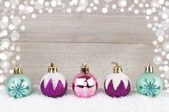 Babioles pourpres, roses et de turquoise de Noël dans la neige contre le bois Photo stock