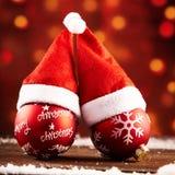Babioles rouges colorées de Noël avec des chapeaux de Santa Photo libre de droits
