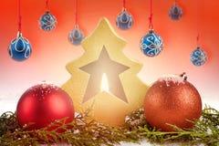 Babioles rouges et bleues de Noël avec la bougie rougeoyante à l'intérieur de l'arbre de Noël décoratif L'atmosphère de fête de v Image stock