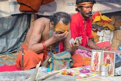 Indian sadhu making up for ritual. BABUGHAT, KOLKATA, WEST BENGAL / INDIA - 10TH JANUARY 2015 : Hindu Sadhu making up for rituals , wearing bindi, a big red dot Royalty Free Stock Image