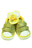 Baby's bootee and pacifier. Green baby's bootee and yellow pacifier on white background Royalty Free Stock Photos