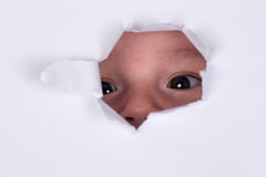 Baby är nyfiken och se till och med ett hål Fotografering för Bildbyråer