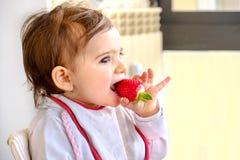 Baby äter den nyfödda jordgubben äter frukt arkivfoton