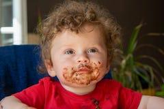 Baby äter en chokladkaka arkivfoto