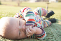 Baby-äußeres Kauen auf Händen Stockbild