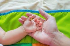 Baby& x27; рука s отдыхает на его father& x27; рука s Чувствуйте тепло стоковая фотография