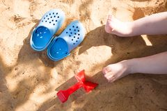 baby& x27;在海滩沙子的s腿,蓝色触发器和玩具铁锹,在沙盒的戏剧 免版税库存照片