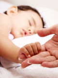 Baby. Sleeping take the hand of her mother Stock Image