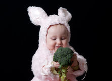 Baby. Portrait of the baby girl in bunny costume with broccoli Stock Image