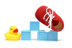 Baby. The word baby is isolated on white with a rubber ducky and a red shoe Royalty Free Stock Photos