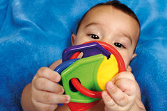 Baby. Happy baby with toy on a blue tonel royalty free stock images