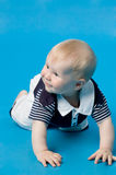 Baby. The small smiling child in studio, on a blue background Royalty Free Stock Images