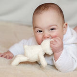 Baby. Portrait of a cute 6 month old baby, boy or girl, lying on her belly, lifting her head,  playing with a soft toy rabbit Royalty Free Stock Photos