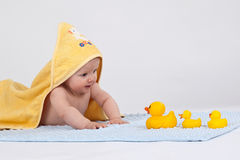 Baby with 3 yellow ducks. Baby with a yellow towel and ducks Royalty Free Stock Photography