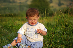 Baby. Cute baby sitting in the grass and crying Royalty Free Stock Images