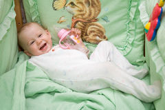 Baby. With bottle smiling in the bed Stock Image